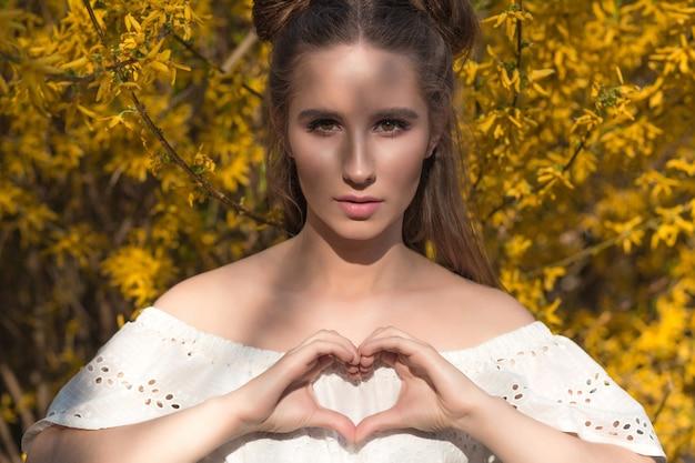 Attraktive brünette frau mit schönem make-up, das herzform an ihren händen zeigt