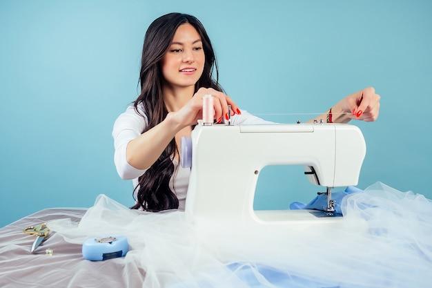 Attraktive brünette frau schneiderin schneiderin fädeln die nadel an der nähmaschine auf blauem hintergrund im studio. das konzept der schaffung einer neuen kleiderkollektion.