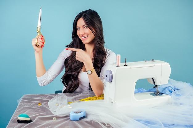 Attraktive brünette frau schneiderin (schneiderin) hält schere und schneidet stoff auf dem tisch mit nähmaschine auf blauem hintergrund im studio.