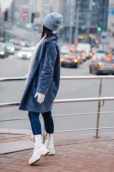 Attraktive brünette frau trägt trendigen wintermantel und hut mit blick auf den stadtverkehr am abend
