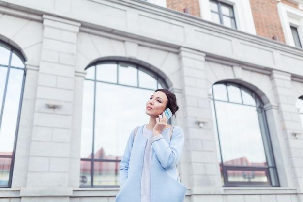 Attraktive brünette geschäftsfrau, die mit dem kunden im hintergrund des bürogebäudes telefoniert