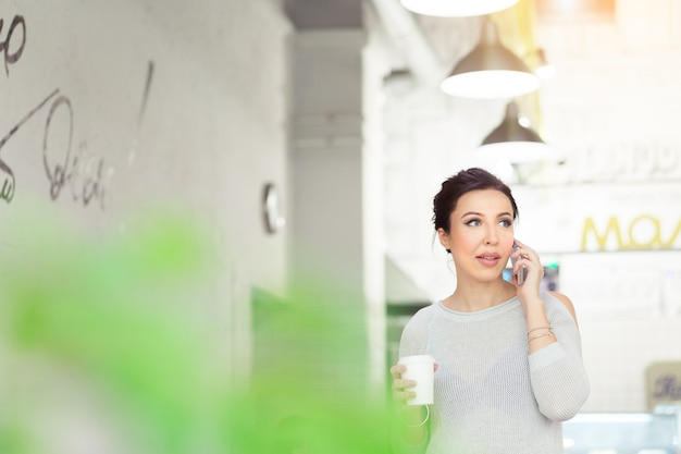 Attraktive brünette geschäftsfrau, die mit dem kunden im modernen café telefoniert