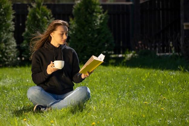 Attraktive brünette im schwarzen kapuzenpulli, der auf graslesbuch, tasse kaffee sitzt