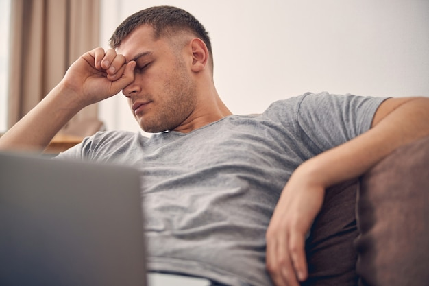 Attraktive brünette männliche geschlossene augen, nachdem sie zeit mit laptop verbracht
