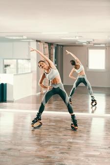 Attraktive brünette mit pferdeschwanz, in sportbekleidung und kängurusprüngen, die sich im fitnessstudio dehnen