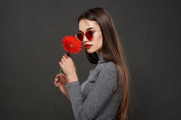 Attraktive brünette rote blume glamour-kosmetiknahaufnahme