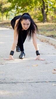 Attraktive brünette sportlerin in der startposition hockte sich hin und wartete darauf, in einem rennen oder wettkampf zu laufen