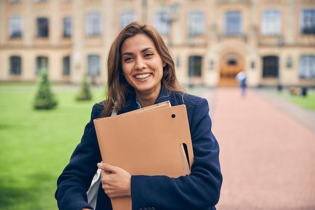 Attraktive brünette studentin mit papieren in den händen, die glücklich aussieht, während sie bei warmem wetter in der nähe eines schönen gebäudes steht