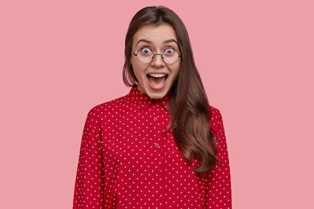 Attraktive brünette überglückliche frau öffnet den mund und schreit vor freude, trägt rosa gepunktete bluse, brille, froh über ihren erfolg