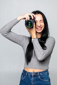 Attraktive brünette zielt auf ihre kamera. komponieren eines fotos im studio, isoliert auf grauer wand