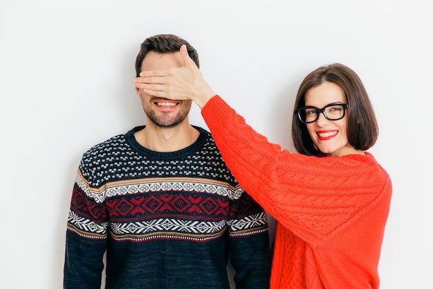 Attraktive brunettefrau mit positivem ausdruck, bedeckt mann `s augen, abnutzungswinterstrickjacken