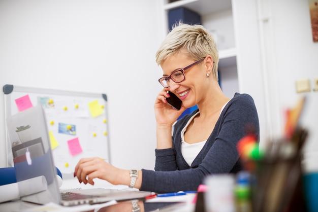 Attraktive charmante blonde geschäftsfrau mit kurzen haaren, die auf einem handy spricht, während sie am schreibtisch sitzt und an einem laptop arbeitet.