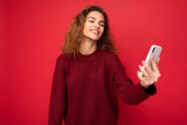 Attraktive charmante junge lächelnde glückliche frau, die das handy hält und benutzt, das selfie trägt, das stilvolle kleidung einzeln über dem wandhintergrund trägt