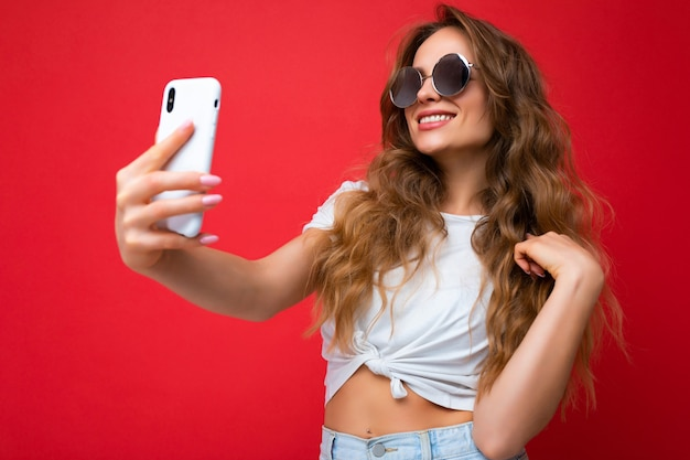 Attraktive charmante junge lächelnde glückliche frau, die das handy hält und benutzt, das selfie trägt, das stilvolle kleidung einzeln über wandhintergrund trägt.
