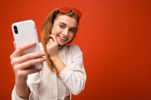 Attraktive charmante junge lächelnde glückliche frau, die das handy hält und benutzt, das selfie trägt