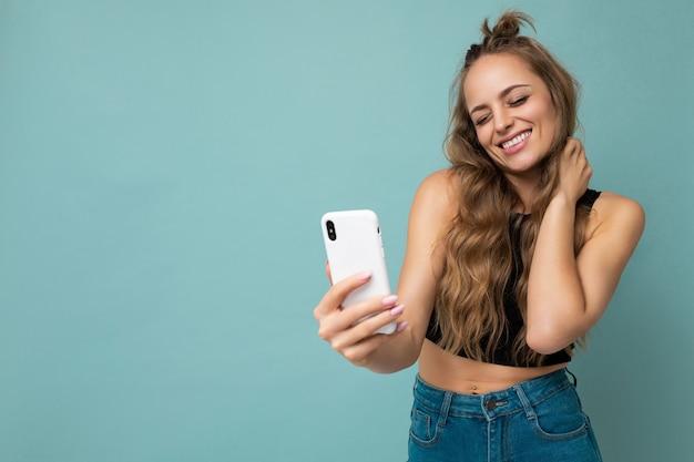 Attraktive charmante junge lächelnde glückliche frau, die handy hält und benutzt, das selfie trägt, das stilvolle kleidung trägt