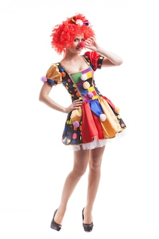 Attraktive clownin mit roten haaren auf weißem hintergrund