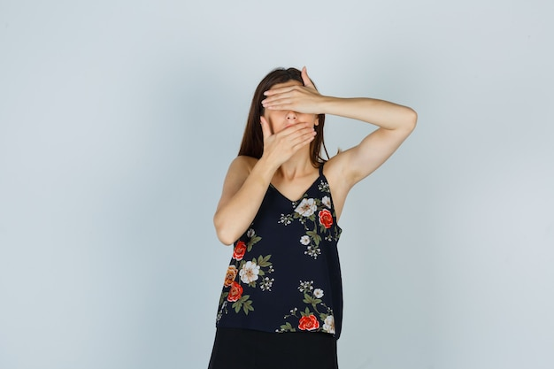 Attraktive dame, die augen und mund mit den händen in der bluse bedeckt und verängstigt aussieht. vorderansicht.