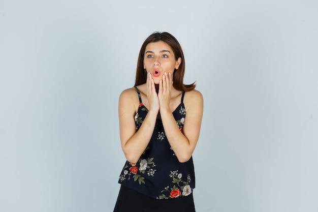 Attraktive dame, die die hände am kinn hält, während sie den mund in der bluse öffnet und schockiert aussieht. vorderansicht.