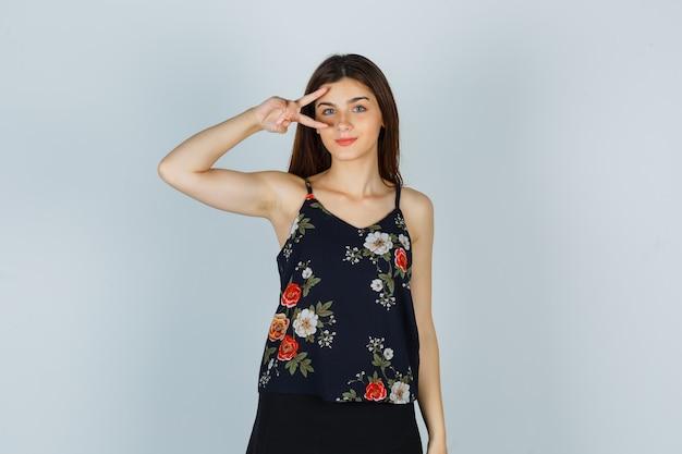 Attraktive dame, die eine v-geste auf dem auge in der bluse zeigt und fröhlich aussieht. vorderansicht.