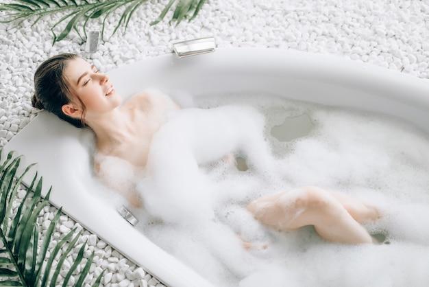 Attraktive dame, die im bad mit schaum, draufsicht liegt