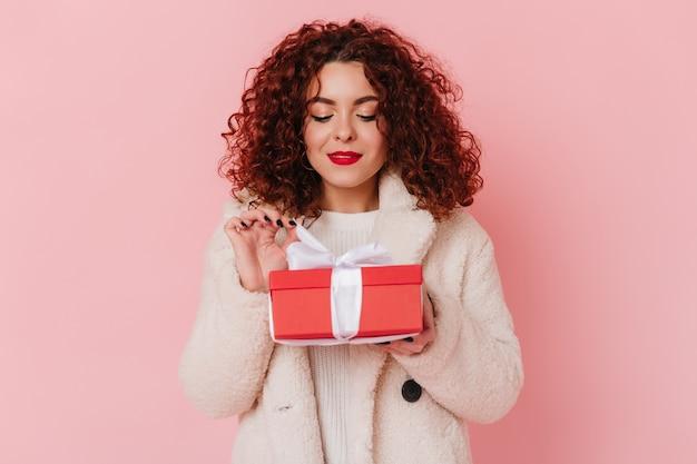 Attraktive dame, die rote geschenkbox mit weißem band auf rosa raum hält. schnappschuss eines lockigen mädchens mit leichtem wolloutfit.