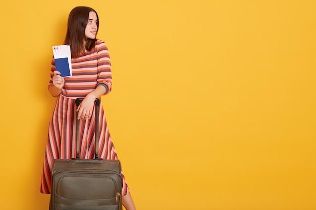 Attraktive dame im gestreiften kleid mit pass und tickets, steht mit koffer an der gelben wand und schaut zur seite
