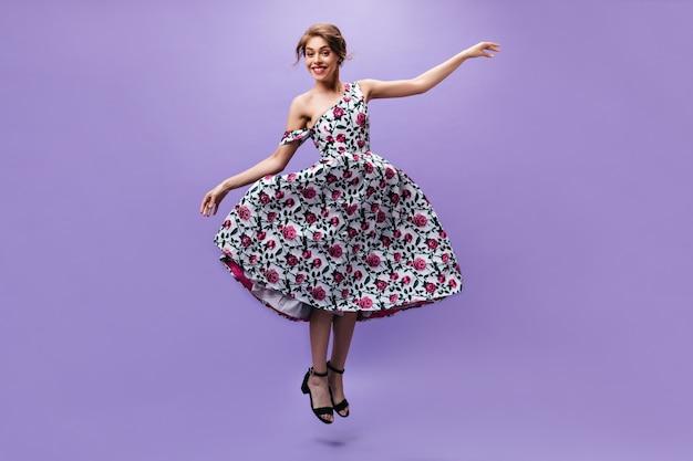 Attraktive dame im herrlichen kleid, das auf lila hintergrund springt. wunderbare junge frau in hellen modischen kleidern, die aufwerfen.