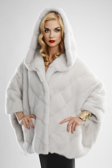 Attraktive dame im weißen pelzmantel mit kapuze auf dem kopf
