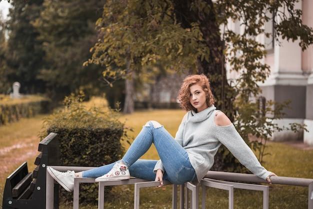 Attraktive dame in der straßenbekleidung, die beine auf schiene sitzt und setzt