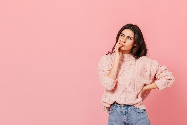 Attraktive dame in hellem outfit denkt über neue idee nach. frau im pullover, der nachdenklich auf rosa hintergrund aufwirft.