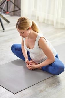Attraktive dame in sportbekleidung, die zu hause trainiert, streckt die körpermuskulatur