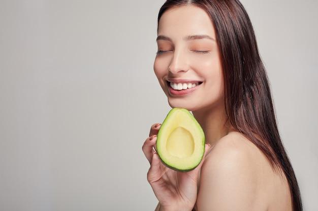 Attraktive dame mit avocado lächelnd mit den zähnen