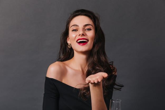 Attraktive dame mit lockigem haar im dunklen oberteil lacht und schaut in die kamera auf schwarzem hintergrund.
