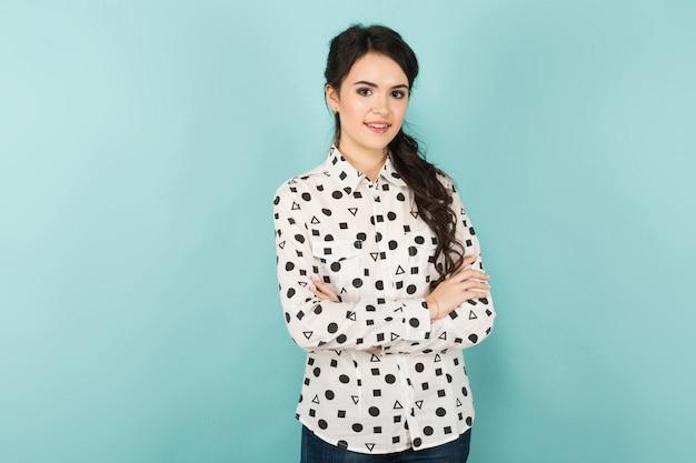 Attraktive dünne brunettefrau in der weißen bluse mit geomitrischen zahlen auf ihr und schwarzer hose