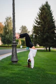 Attraktive dünne frau, die einen backbend macht, während sie einen salto zeigt.
