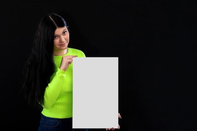Attraktive dunkelhaarige frau in bunten kleidern mit einem weißen leeren plakat, lokalisiert auf einem dunklen hintergrund