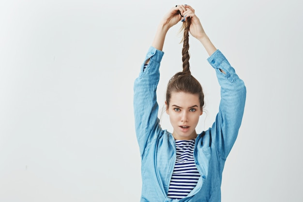 Attraktive ehrgeizige selbstbewusste junge frau, die verdrehte haare hochzieht und gewagte sexy kamera sieht, trendige lose kleidung trägt, zufriedenes ergebnis beim anwenden neuer shampoo-haarpflege,