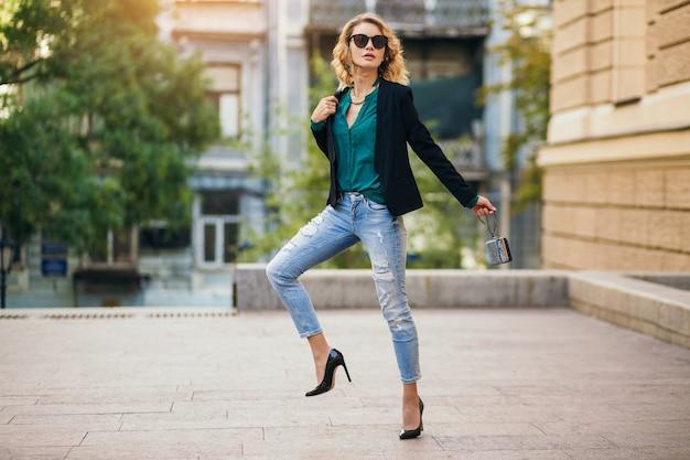 Attraktive elegante frau, die in der stadtstraße auf hochhackigen schuhen, wesaring blauen jeans, schwarzer jacke, grüner bluse, sonnenbrille, kleinen geldbeutel, modetrend des sommers, schlanke schöne dame geht