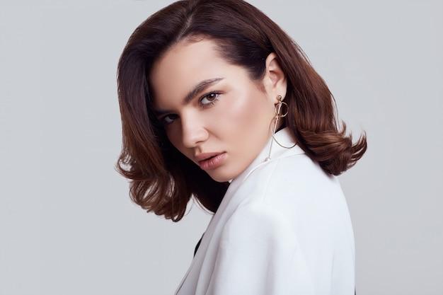 Attraktive elegante frau mit weißem anzug des dunklen haares in mode