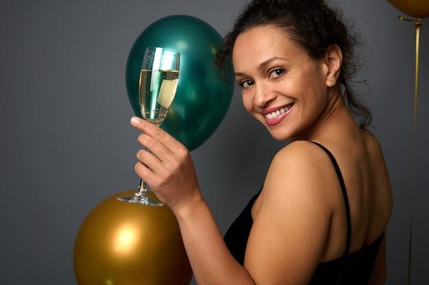 Attraktive elegante frau steht zu drei vierteln gegen eine graue wand und lächelt, schaut über ihre schulter in die kamera und posiert mit einer champagnerflöte vor einem hintergrund aus goldenen und metallisch grünen ballons