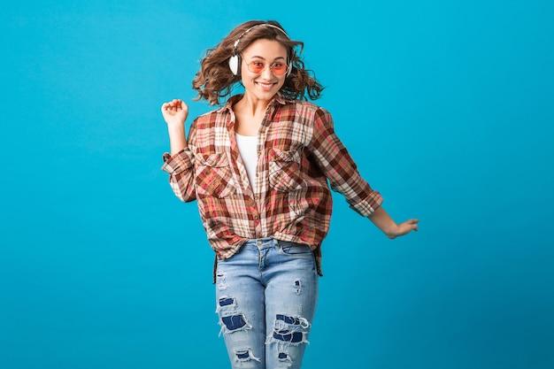 Attraktive emotionale frau, die mit lustigem verrücktem gesichtsausdruck im karierten hemd und in den jeans lokalisiert auf blauem studiohintergrund springt, der rosa sonnenbrille trägt