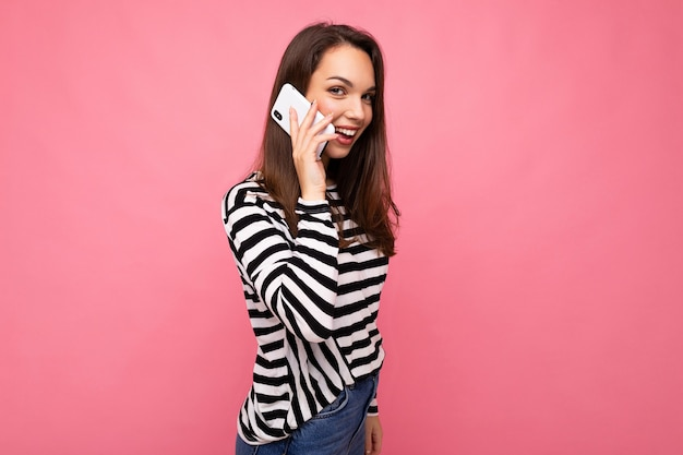 Attraktive emotionale junge frau, die auf dem smartphone spricht, das gestreiften pullover trägt