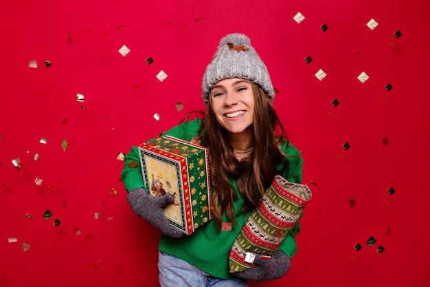 Attraktive energie junge dame, die winteroutfit hält, das feiertagsgeschenke über isoliertem rotem hintergrund mit konfetti, feier, neujahr, geburtstag, glücklicher stimmung trägt