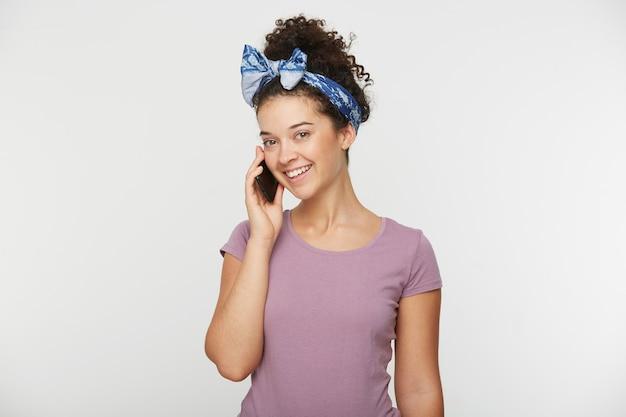 Attraktive entzückende brünette frau mit lockigem haar im lässigen t-shirt und im stirnband, die mit jemandem speziell am telefon sprechen