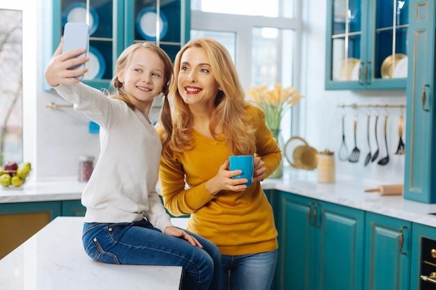 Attraktive entzückte blonde schlanke mutter, die lächelt und eine tasse tee hält, während ihre tochter selfies nimmt
