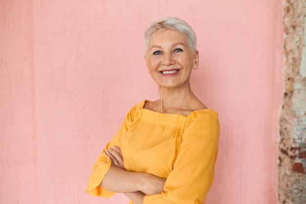 Attraktive erfolgreiche blonde geschäftsfrau mittleren alters mit kurzen pixie-haaren und charmantem selbstbewusstem lächeln, das isoliert gegen leeren rosa wandhintergrund posiert und arme auf ihrer brust verschränkt hält