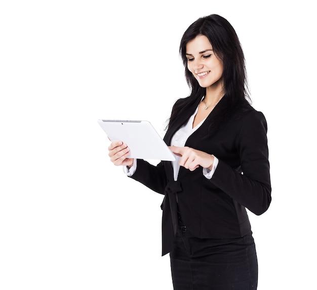 Attraktive, erfolgreiche geschäftsfrau, die einen geschäftsplan auf der tablette auf einem weißen hintergrund studiert