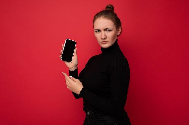 Attraktive ernsthafte junge brünette frau, die schwarzen pullover trägt, der isoliert über roter wand steht und handy mit leerem bildschirm zeigt.