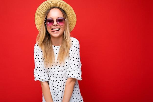 Attraktive, erstaunliche, lustige junge blonde frau, die alltägliche stilvolle kleidung und moderne sonnenbrillen trägt, die auf einer bunten hintergrundwand mit blick auf die kamera isoliert sind